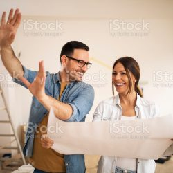 Young couple standing in their apartment while woman holding blueprint and man showing to her new ideas.